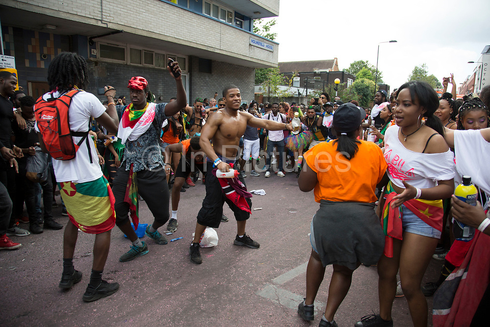 Forming a circle which then everyone rushes into, in an explosion of joyous dancing on Monday 28th August 2016 at the 50th Notting Hill Carnival in West London. A celebration of West Indian / Caribbean culture and Europes largest street party, festival and parade. Revellers come in their hundreds of thousands to have fun, dance, drink and let go in the brilliant atmosphere. It is led by members of the West Indian / Caribbean community, particularly the Trinidadian and Tobagonian British population, many of whom have lived in the area since the 1950s. The carnival has attracted up to 2 million people in the past and centres around a parade of floats, dancers and sound systems.