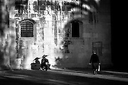 MONOCHROME<br /> Elderly woman walking past scooter and ancient cathedral wall.<br /> Trogir, Croatia