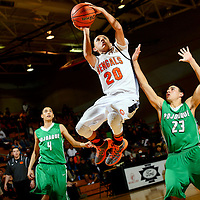 010914  Adron Gardner/Independent<br /> <br /> Gallup Bengal Ronald Lee (20) floats past Pojoaque Elk Chris Martinez (23) during the Gallup Invitational boys basketball tournament in Gallup Thursday.