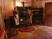 Living History Park Ranger Yvonne Heaton preparing woodstove for baking, Cheese Room, Winsor Castle, Pipe Spring National Monument, Arizona.