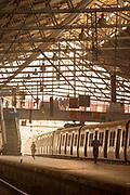 View of train station and people running towards train, Mumbai, India