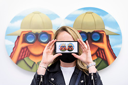 """© Licensed to London News Pictures. 13/05/2021. LONDON, UK.  London, UK.  13 May 2021. A staff member poses with  """"Vesica"""", 2021, by Julie Curtiss.  Preview of """"Monads and Dyads"""", the first London exhibition by New York-based artist Julie Curtiss.  Her surrealist works feature new paintings, works on paper and sculptures.  The show is at White Cube Mason's Yard in Mayfair 14 May to 26 June 2021.  Photo credit: Stephen Chung/LNP"""