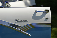 Old Westbury, New York. United States. 7th June 2015. A blue and white 1956 Ford Victoria two-door sedan, its driver side door seen in closeup with chrome trim and emblem, is shown at the 50th Annual Spring Meet Car Show sponsored by Greater New York Region Antique Automobile Club of America. Over 1,000 antique, classic, and custom cars participated at the popular Long Island vintage car show held at historic Old Westbury Gardens.