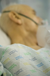 Elderly patient in a hospital bed with an oxygen mask on.
