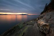 Sunset over Lummi Island and sandstone Tafoni at Clayton Beach in Larrabee State Park - Bellingham, Washington State, USA