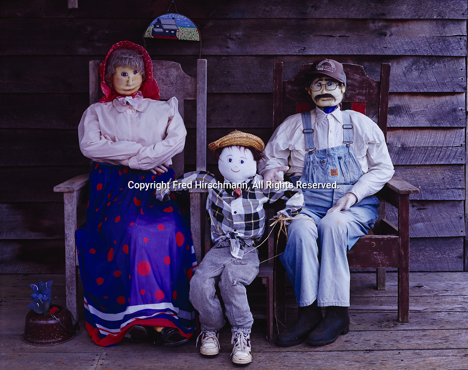 Hay-stuffed Ozark folk family made by Linda Williams, sitting on the porch of the Country Palace Ozark Crafts Store, Pelsor, Arkansas.
