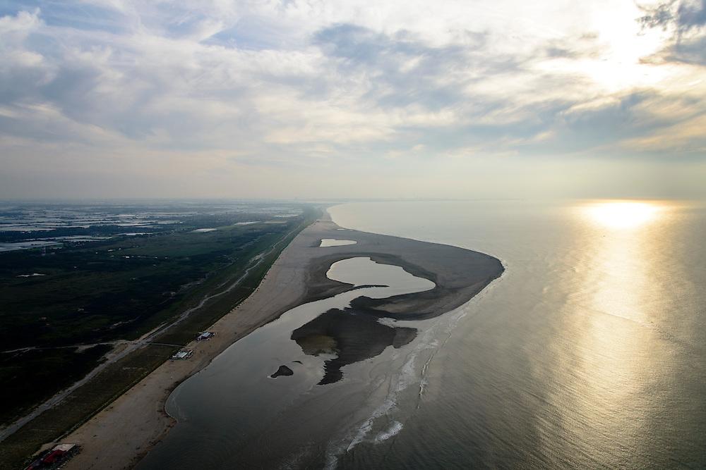 Nederland, Zuid-Holland, Gemeente Westland,  28-09-2014; Delflandse Kust ter hoogte van Ter Heijde en Monster. Maasvlakte aan de horizon, links de kassen van het Westland.<br /> De Zandmotor is den kunstmatig schiereiland ontstaan door het opspuiten van zand voor de kust. Wind, golven en stroming zullen het zand langs de kust verspreiden waardoor breder stranden en duinen ontstaan. De zandmotor is een experiment in het kader van kustonderhoud en kustverdediging. <br /> Sand Engine, artificial peninsula build by the raising of sand for the coast of Ter Heijde (near the Hague). Wind, waves and currents will distribute the sand along the coast yielding wider beaches and dunes along the coastline. The Sand Engine is a experiment for coastal maintenance of coastal defense.<br /> luchtfoto (toeslag op standard tarieven);<br /> aerial photo (additional fee required);<br /> copyright foto/photo Siebe Swart