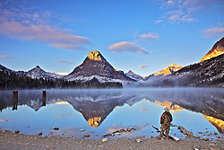 A visitor takes in the view of  Mt. Sinopah reflection on Two Medicine Lake in Glacier National Park.