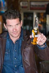 Man in a leather jacket offering up a bottle of beer