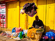 05 MARCH 2017 - KATHMANDU, NEPAL: A marigold garland vendor sells his flowers in front of a set of yellow doors in Kathmandu.     PHOTO BY JACK KURTZ