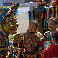 A Tibetan Buddhist Tsam dancer dressed as Bisman tengri, the god of wealth, entertains his companions as they  wait to perform at the national Naadam festival in Ulaanbaatar, Mongolia.
