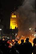 Fires burning on Whitehall fill the air with smoke .National student demonstration in London, protesting against tuition fees and the threat of top-up fees. Students from all over the UK gathered in central London for a second mass demo in protest of the coalition govenrnment's plans for education funding. Centred around Whitehall the protest was partly peaceful but also marred by arrests and some violence.