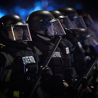 Police officers stand the line in riot gear near the Minneapolis Police third precinct after a white police officer was caught on a bystander's video pressing his knee into the neck of African-American man George Floyd, who later died at a hospital, in Minneapolis, Minnesota, U.S. May 28, 2020. REUTERS/Adam Bettcher