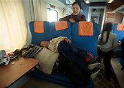 A Tibetan family makes jokes as they travel to Lhasa aboard a train from Beijing.