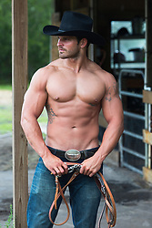 shirtless cowboy in a barn holding horse reins