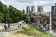 """York's 4-kilometer long medieval town walls are the longest in England. In the background is York Minster, built over 250 years 1220-1472 AD, one of the finest medieval buildings in Europe. Also known as St Peter's, its full name is """"Cathedral and Metropolitical Church of St Peter in York,"""" located in England, United Kingdom, Europe. York Minster is the seat of theArchbishop of York, the second-highest office of the Church of England.""""Minster"""" refers to churches established in the Anglo-Saxon period as missionary teaching churches, and now serves as an honorific title.York was founded by the Romans as Eboracum in 71 AD. As the center of the Church in the North, York Minster has played an important role in great national affairs, such as during the Reformation and Civil War."""