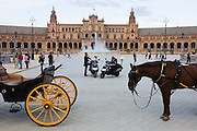 Policemen make calls from their scooters near horse and carriages in Seville's Plaza de Espana.