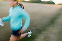 Blurry young woman running with MP3 player.