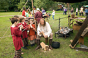 Man teaching children woodcraft, Historical re-enactment Saxon, Viking, Norman history, Woodbridge, Suffolk