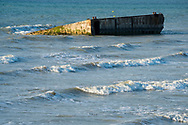 Remains of Mulberry Harbour in Arromanches, Normandy, France. In the days after D-Day, the Allies built a large artificial port, the remains of which are still visible.