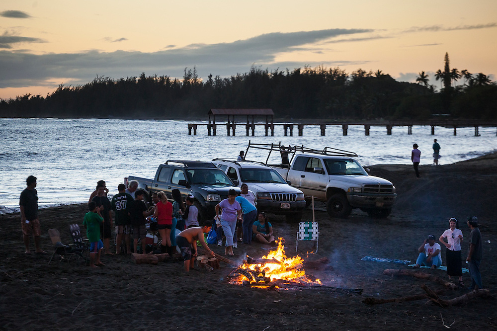Locals gather for a bonfire and tailgate party on the beach in Waimea, Kauai, Hawaii.