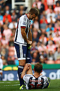 Gareth McAuley of West Bromwich Albion helps Craig Dawson of West Bromwich Albion who is suffering from cramps. Barclays Premier League match, Stoke city v West Bromwich Albion at the Britannia stadium in Stoke on Trent, Staffs on Saturday 29th August 2015.<br /> pic by Chris Stading, Andrew Orchard sports photography.
