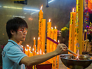 23 SEPTEMBER 2014 - BANGKOK, THAILAND: A man prays on the first day of the Vegetarian Festival at the Chit Sia Ma Chinese shrine in Bangkok. The Vegetarian Festival is celebrated throughout Thailand. It is the Thai version of the The Nine Emperor Gods Festival, a nine-day Taoist celebration beginning on the eve of 9th lunar month of the Chinese calendar. During a period of nine days, those who are participating in the festival dress all in white and abstain from eating meat, poultry, seafood, and dairy products. Vendors and proprietors of restaurants indicate that vegetarian food is for sale by putting a yellow flag out with Thai characters for meatless written on it in red.    PHOTO BY JACK KURTZ