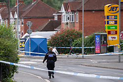CAPTION UPDATE © Licensed to London News Pictures. 31/07/2021. High Wycombe, UK. A police officer walks towards a forensic tent outside a Jet petrol station on Micklefield Road as a murder investigation is launched in High Wycombe following the discovery by a police patrol of a person on the ground at approximately 12:20BST surrounded by a group of males who fled the scene when the police officers arrived, despite the efforts of police and paramedics the man died at the scene. Photo credit: Peter Manning/LNP