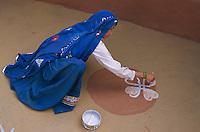 Inde. Rajasthan. Village dans les environs deTonk. Une femme peint le sol de sa maison pour la fête de nouvel année. // India. Rajasthan. Village near Tonk. Woman painting house ground for new year festival (Diwali).