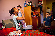 Adriana (25) with her two years old daughter Anna Kristina and son Ondrej (4) in the living room of their family in a building at Lunik IX.