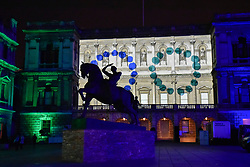 """© Licensed to London News Pictures. 17/01/2018. LONDON, UK.  The new equestrian statue """"Physical Energy"""" by George Frederic Watts RA is seen in silhouette against """"Love Motion"""" by Rhys Coren, a projection onto the Royal Academy in Piccadilly. Preview of Lumiere London, the capital's largest arts festival commissioned by The Mayor of London and produced by Artichoke.  Light installations by leading artists have been set up, both north and south of the river for the public to view 18-21 January.   Photo credit: Stephen Chung/LNP"""