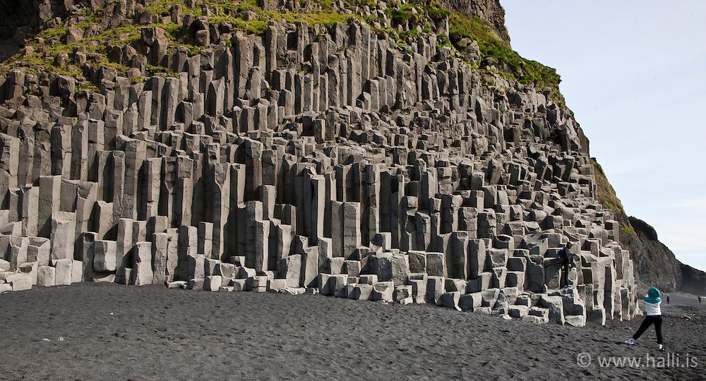 Tourists at the beach Reynisfjara, columnar basalt in the back - Stuðlaberg og ferðamenn í Reynisfjöru
