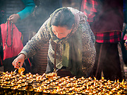 17 MARCH 2017 - KATHMANDU, NEPAL: A woman lights butter lamps at a Tibetan Buddhist monastery next to Boudhanath Stupa in Kathmandu. Boudhanath Stupa is the holiest site in Nepali Buddhism. It is also the center of the Tibetan exile community in Kathmandu. The Stupa was badly damaged in the 2015 earthquake but was one of the first buildings renovated.      PHOTO BY JACK KURTZ