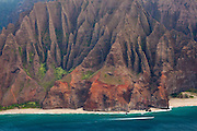 A tour boat is dwarfed by the fluted cliffs of the Na Pali Coast, Kauai, Hawaii.