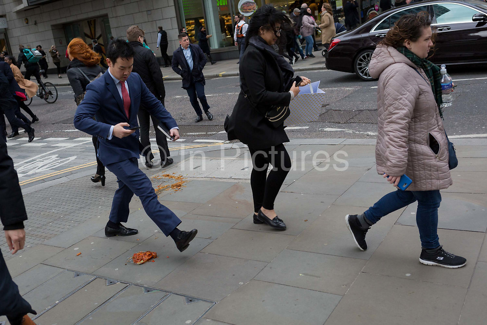 Pedestrians avoid a noodle and sauce takeaway, dropped and discarded on the pavement during lunch-hour in the capitals financial district, on 4th February 2020, in the City of London, England. The lunchtime meal was being carried along the street when its heat and moisture made it drop through the bottom of a paper bag, turning it upside down and lying perfectly on the pavement as city workers emerged from their offices. Those who saw it in time stepped over the greasy obstacle but the distracted mostly by walking with phones to ears, stepped in it and helping spread it across the pavement.