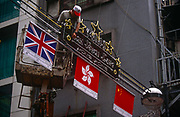 The flags of Britain, Hong Kong and Peoples Republic of China fly together above the streets of Central, the day after the Handover of sovereignty from Britain to China, on 30th June 1997, in Hong Kong, China. Midnight signified the end of British rule, and the transfer of legal and financial authority back to China. Hong Kong was once known as fragrant harbour or Heung Keung because of the smell of transported sandal wood.