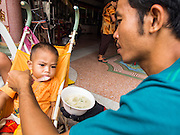 """07 AUGUST 2014 - BANGKOK, THAILAND:      A man gives dessert to his son during a food distribution at Pek Leng Keng Mangkorn Khiew Shrine in Bangkok. Thousands of people lined up for food distribution at the Pek Leng Keng Mangkorn Khiew Shrine in the Khlong Toei section of Bangkok Thursday. Khlong Toei is one of the poorest sections of Bangkok. The seventh month of the Chinese Lunar calendar is called """"Ghost Month"""" during which ghosts and spirits, including those of the deceased ancestors, come out from the lower realm. It is common for Chinese people to make merit during the month by burning """"hell money"""" and presenting food to the ghosts. At Chinese temples in Thailand, it is also customary to give food to the poorer people in the community.   PHOTO BY JACK KURTZ"""