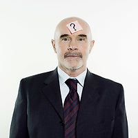 studio portrait isolated on white background of a man senior having a post-it with a question mark on his head