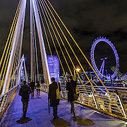 Camminando sul Golden Jubilee Bridges, sullo sfondo la ruota panoramica London Eye<br /> <br /> Walking on the Golden Jubilee Bridges, the Ferri wheel London Eye on background.