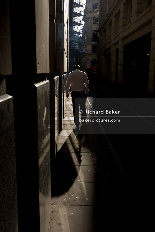 A male office worker walks through a shaft of early spring light in a side street in the capital's financial district. This is Lombard Street, originally a piece of land granted by King Edward I to goldsmiths from the part of northern Italy known as Lombardy (larger than the modern region of Lombardy). It is a narrow and usually dark sidestreet near the Bank of England in the heart of what is called the Square Mile - the inner-part and oldest quarter of London occupied first by the Romans 2,000 years ago. Nowadays the City of London is home to banks and financial institutions but also with a resident population of under 10,000 but a daily working population of 311,000.
