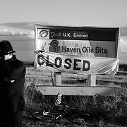 The sign for Shell Haven Oil Site defaced with green paint. An oil tanker can be seen in the back ground behind the depondend police officer...Crude Oil Awakening is a coalition of climate change activist groups. On Saturday Oct 16 they shut the only entrance to Coryton oil refinery in Essex, UK with the aim of highlighting the issues of climate change and the burning of fossil fuels. The blockade meant that a great number of trucks with oil were not able to leave the refinary during the day of action.
