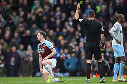 Burnley's Ashley Barnes (left) is booked for unsporting behaviour by referee David Coote during the Premier League match at Turf Moor, Burnley.