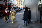 Alternative dressed woman in yellow fluffy slippers on Bishopsgate in the City of London, England, United Kingdom.