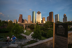 Houston,Texas skyline with people walking on the North Trail of Buffalo Bayou walk in the foreground.