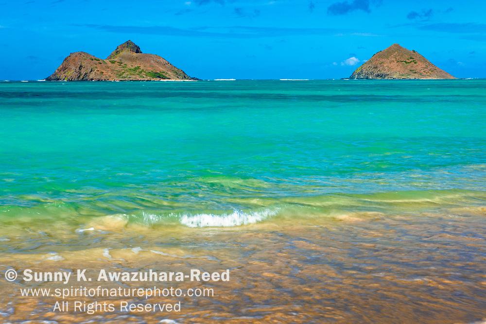 Turquoise color of Lanikai Beach and Mokulua Islands under blue sky, Oahu Island, Hawaii.