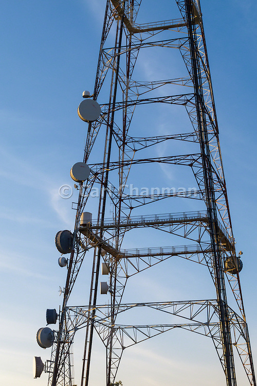 Microwave dish antenna in shadow on television broadcast transmission lattice tower at sunrise on Mt Coot-tha, Brisbane, Queensland, Australia <br /> <br /> Editions:- Open Edition Print / Stock Image