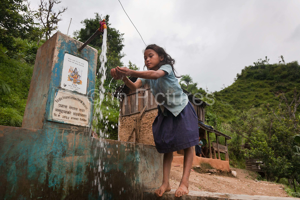 Junmaya Chepang drinks water from a tap and water system provided by Restless Development and their partner NGO Prayash.The Chepangs is an ethnic group which used to be nomadic. Only recently have the settled and their settlements are high up in the mountains.