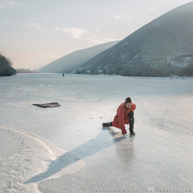 Mongolians play an old version of curling, sliding anklebones on ice. Early morning around the Tuul river, on the edge of Ulan Bator.<br /> Mongolia