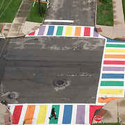 """A person crosses a crosswalk where rainbow pattern is painted at Adams and 13th streets in Toledo on Wednesday, Aug.18, 2021. A ceremony is being held at 5:30 p.m. Wednesday to rename a portion of Adams Street, including where the street is painted, in honor of the late Louis Escobar, the first openly gay man and first Latino elected to Toledo City Council. It will be named """"Louis Escobar Way."""" THE BLADE/KURT STEISS"""