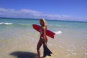 Woman entering ocean with bodyboard<br />
